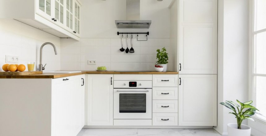 Silver cooker hood in minimal white kitchen interior with plant on wooden countertop. Real photo