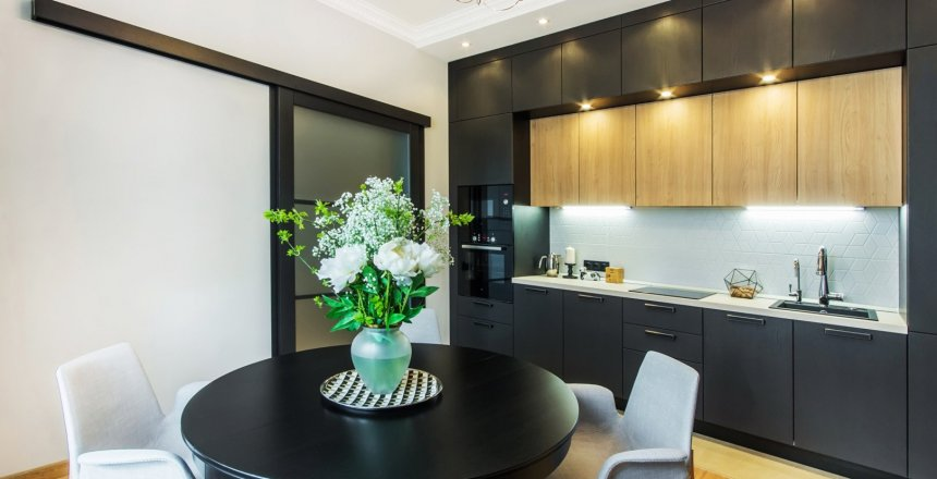Beautiful kitchen in contemporary apartment. Modern interior  with round breakfast table with flowers and sliding door