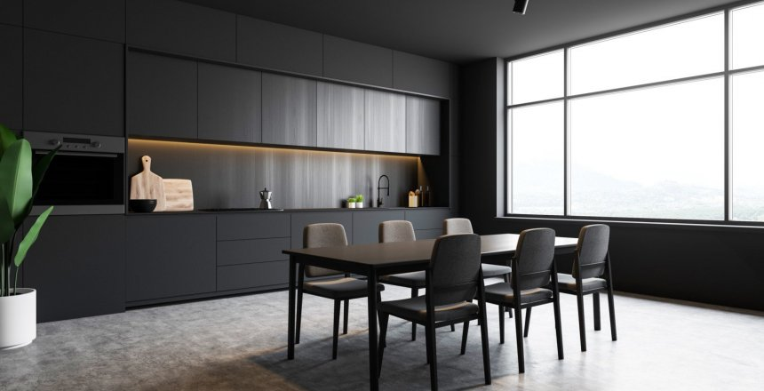 Corner of modern kitchen with gray walls, concrete floor, grey countertops and wooden cupboards, dining table with gray chairs and oven. Large window with mountain view. 3d rendering